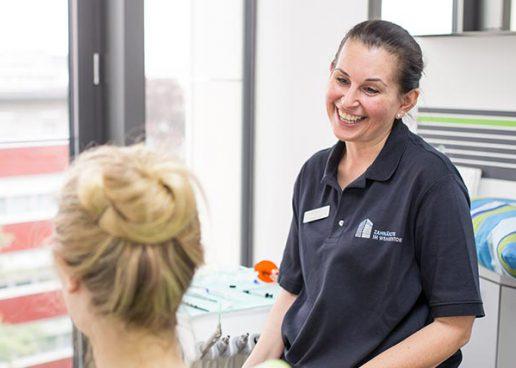 Eine Mitarbeiterin der Zahnarztpraxis Zahnärzte im Wengentor in Ulm unterhält sich mit einer Patientin für eine bessere Mundgesundheit und eine neue Lebensqualität