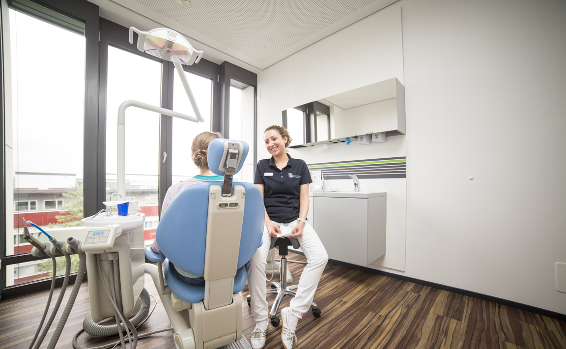Einblick in ein Gespräch zwischen einer Assistentin und Patientin im Behandlungsstuhl der Zahnarztpraxis Zahnärzte im Wengentor in Ulm