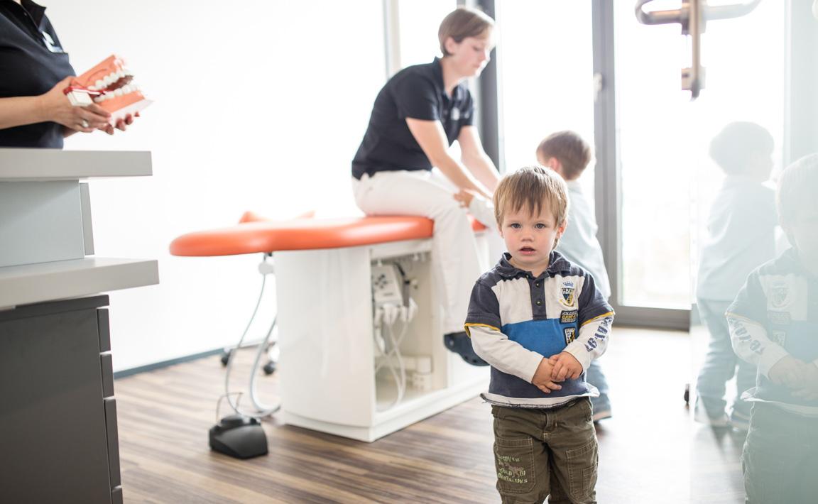 Ein kleiner Junge im Behandlungsraum nach seiner Untersuchung beim Kinderzahnarzt in der Zahnarztpraxis Zahnärzte im Wengentor in Ulm