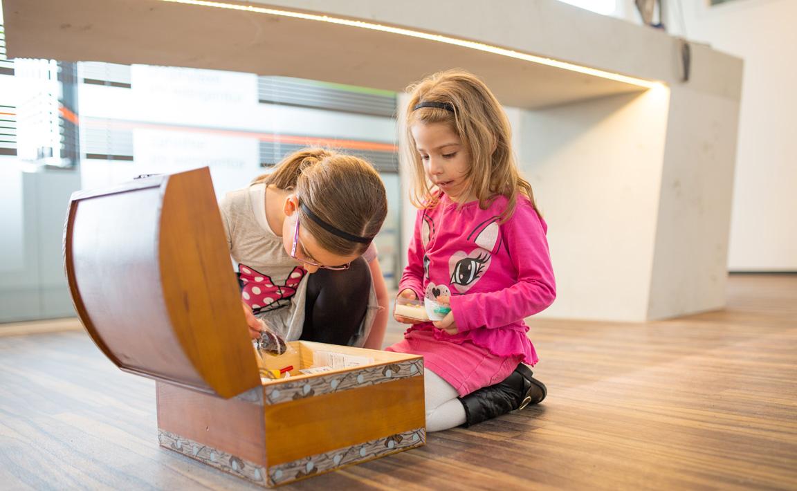 Zwei kleine Mädchen dürfen sich nach ihrem Besuch beim Kinderarzt eine Belohnung aus der Schatztruhe der Zahnarztpraxis Zahnärzte im Wengentor in Ulm aussuchen