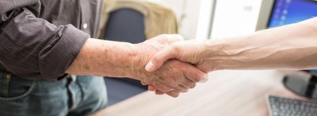Ein Zahnarzt der Zahnarztpraxis Zahnärzte im Wengentor in Ulm reicht einem seiner Partner die Hand für eine gute Zusammenarbeit