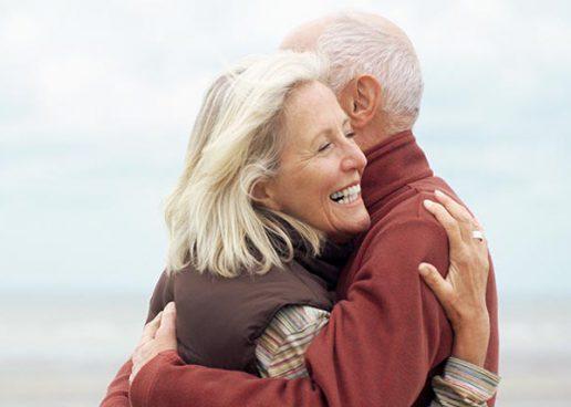 Frau mit natürlichen schönen Zähnen umarmt lächelnd einen Mann