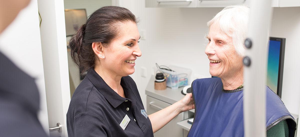 Mitarbeiterin erklärt Frau Besonderheiten der Methode Feste Zähne an einem Tag in Ulm.