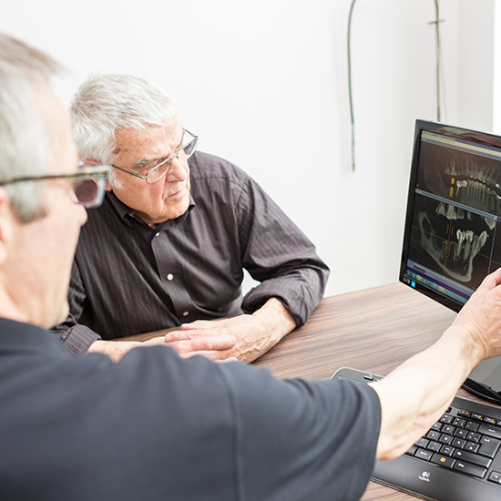 Beratungsgespräch zwischen Zahnarzt und Patienten zum Thema Feste Zähne und Zahnimplantate mit Betrachtung der Röntgenaufnahmen in der Zahnarztpraxis Zahnärzte im Wengentor in Ulm