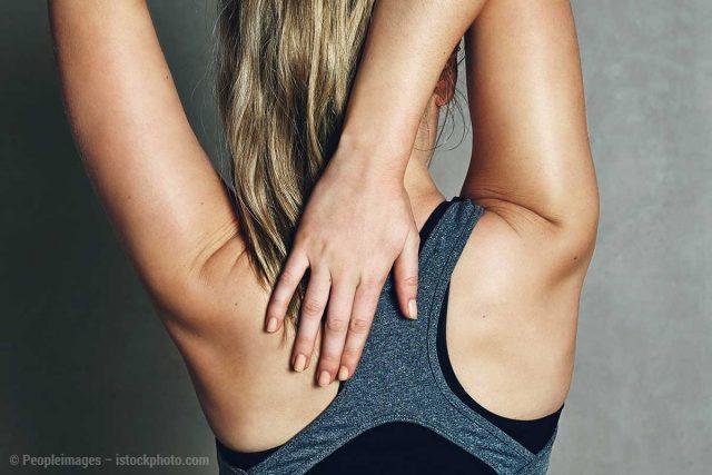 Frau dehnt ihren Rücken für eine bessere Rückengesundheit