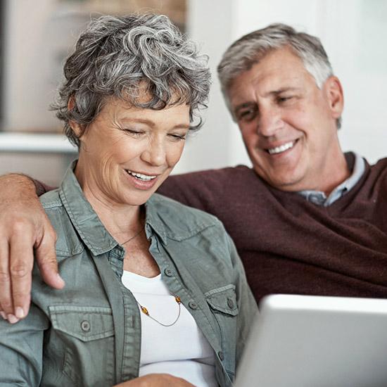 Ein älteres Ehepaar informiert sich über die eine neue Lebensqualität mit Zahnersatz auf Implantaten bei den Zahnärzten im Wengentor in Ulm