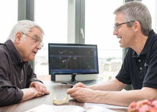 Dr. Christian Scheytt informiert einen Patienten zu festen Zähnen