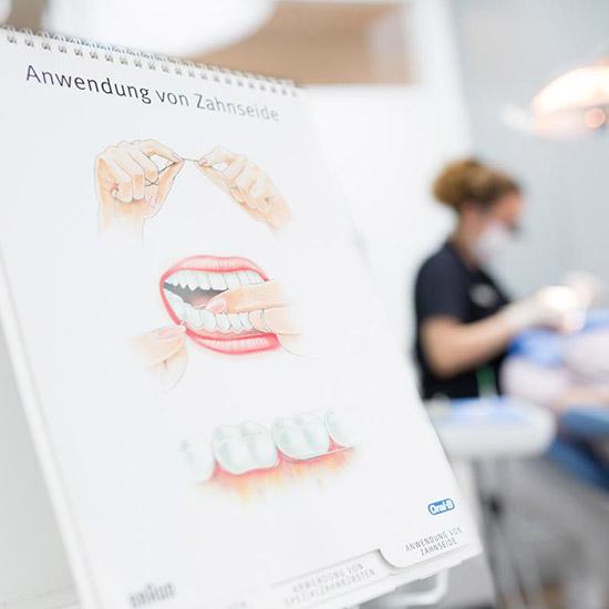 Informationstafel zur Anwendung von Zahnseide für die Prophylaxe der Zahnärzte im Wengentor Ulm