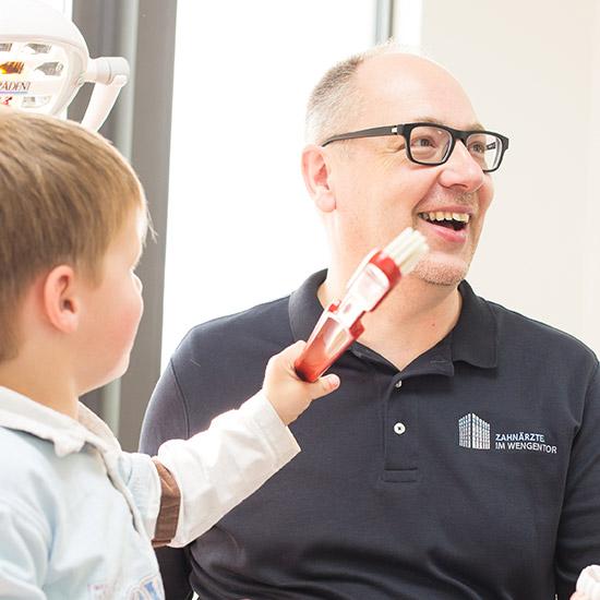 Familienzahnarzt Hans-Georg Stromeyer und kleiner Junge machen Spaß