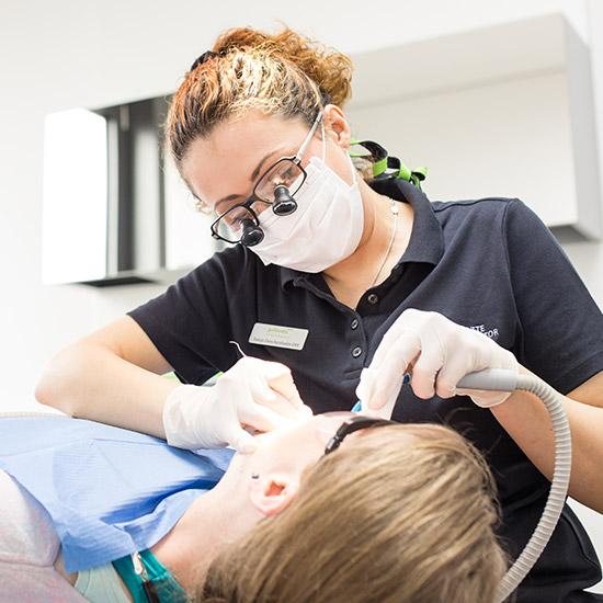 Dentalhygienikerin reinigt die Zähne einer Patienten